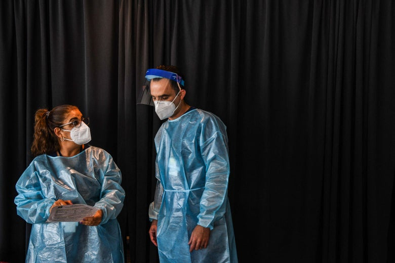 A man and woman wearing masks and surgical gowns look at a clipboard.