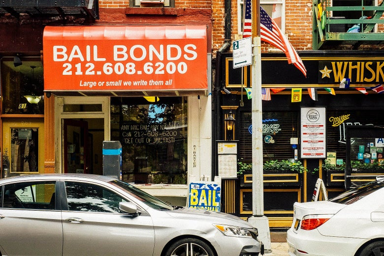 The storefront of a bail bonds shop with cars parked on the street in front of it in New York City.