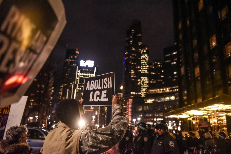 "People hold up signs in front of police at night. One reads, ""ABOLISH I.C.E."""