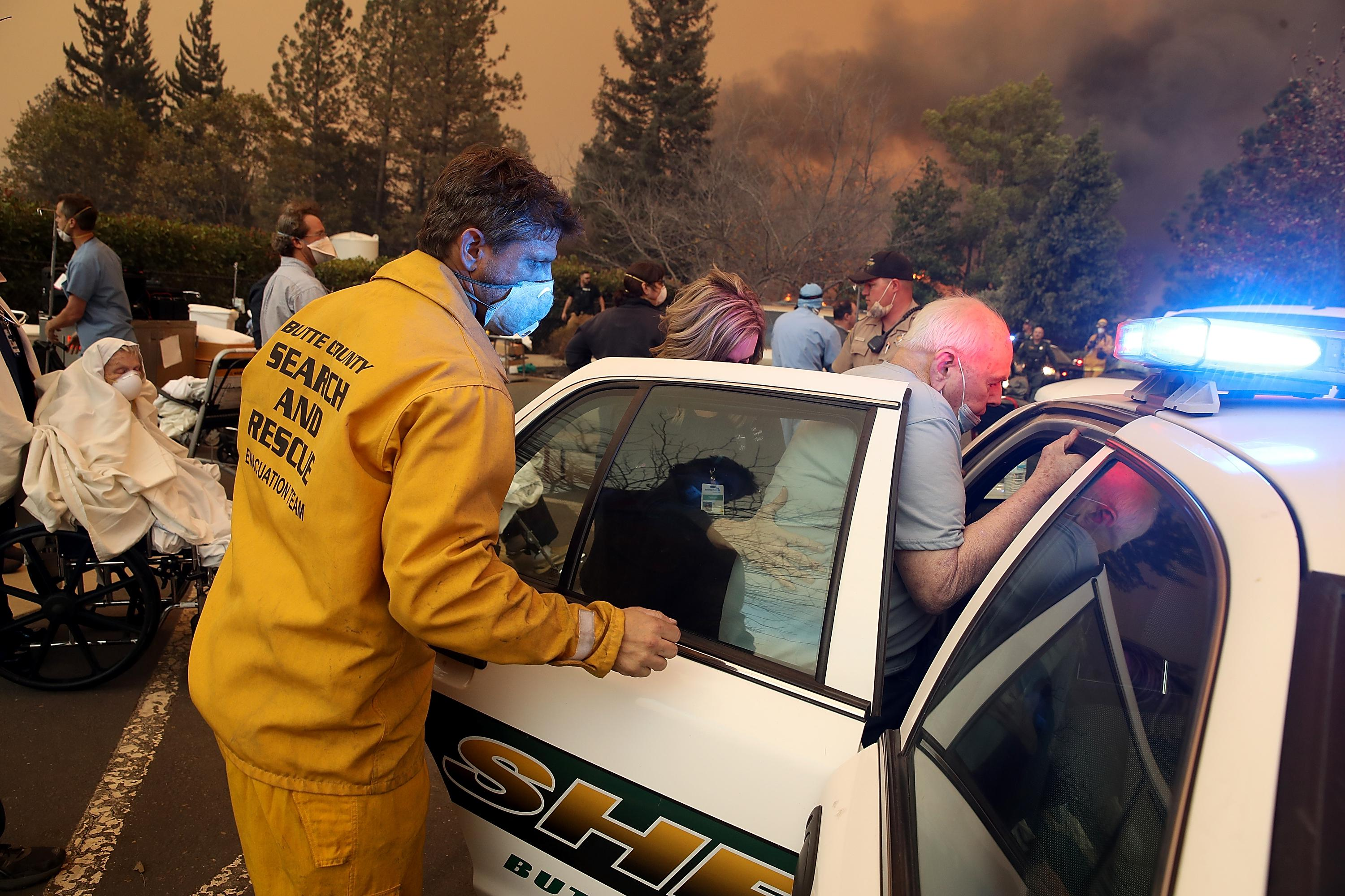 Hospital workers and first responders evacuating patients in a parking lot, with smoke in the background.