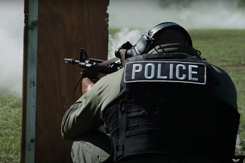 A man in a bulletproof vest holds a sniper rifle out a window.