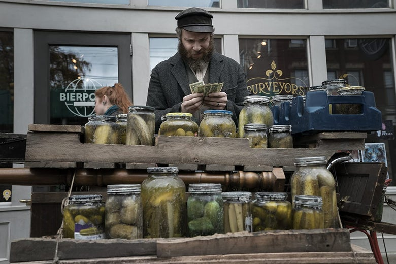 Seth Rogen, with a cap and long beard, holds dollar bills while standing behind a cart loaded with mismatched jars of pickles.