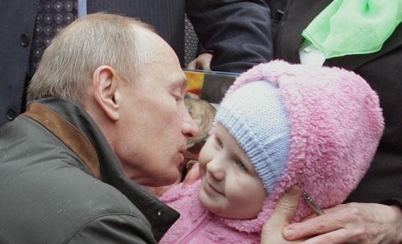 Russian Prime Minister Vladimir Putin kissing a baby