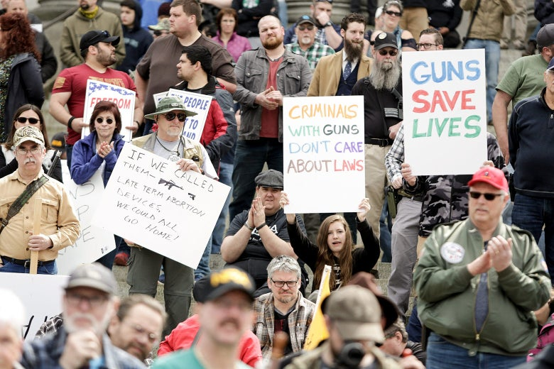 "A crowd of gun rights activists holding signs such as ""Guns Save Lives"" and ""Criminals With Guns Don't Care About Laws."""