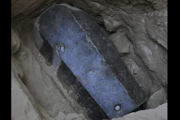 A battered but imposing black coffin-like structure in an excavated rock