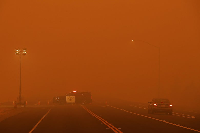 A patrol vehicle on an empty road engulfed in a smoky haze.