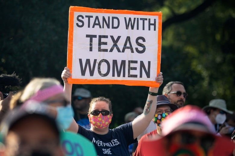 """A protester in a crowd holds up a sign that says, """"STAND WITH TEXAS WOMEN."""""""
