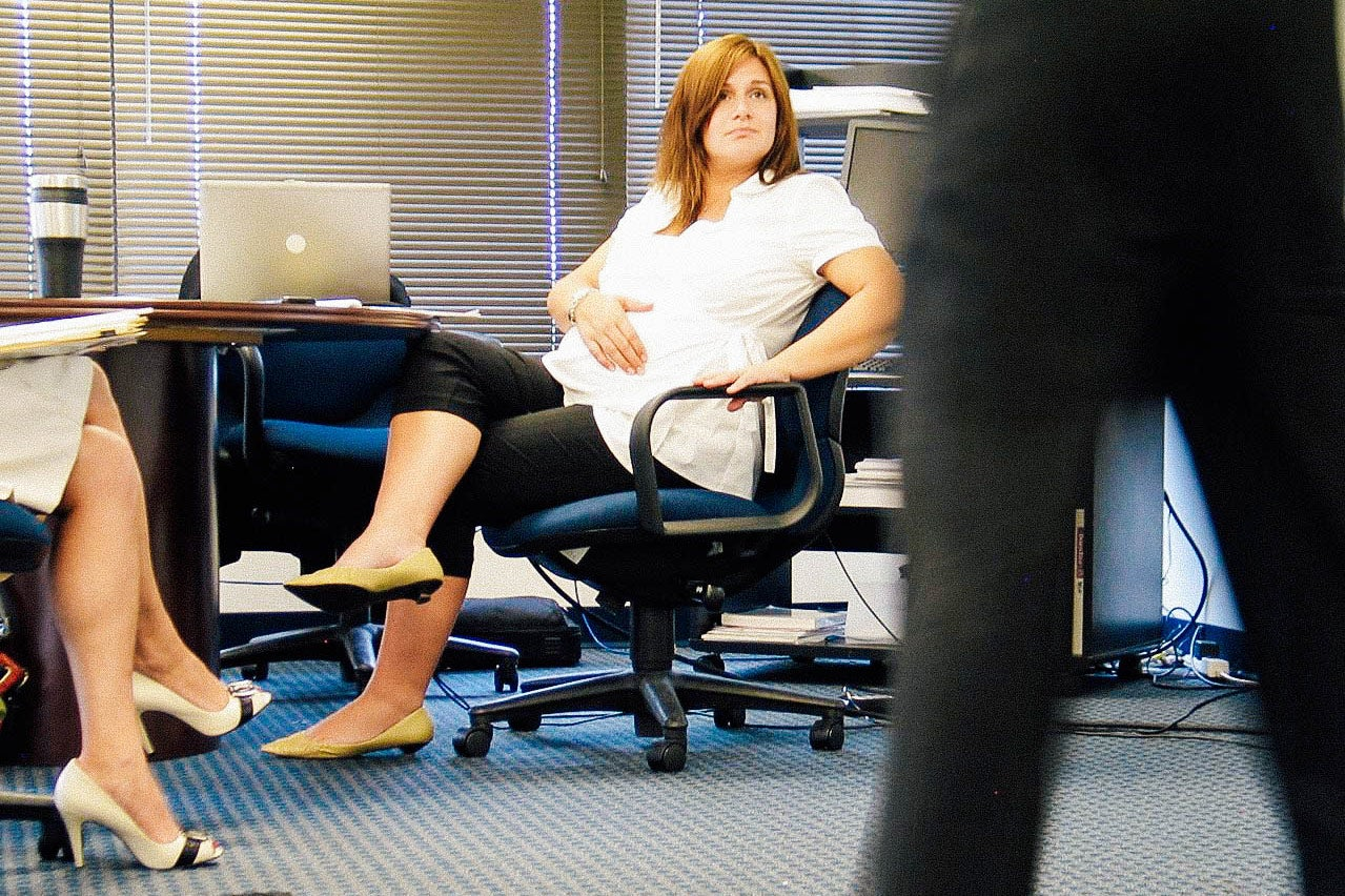 Christine sits in a meeting in an office.