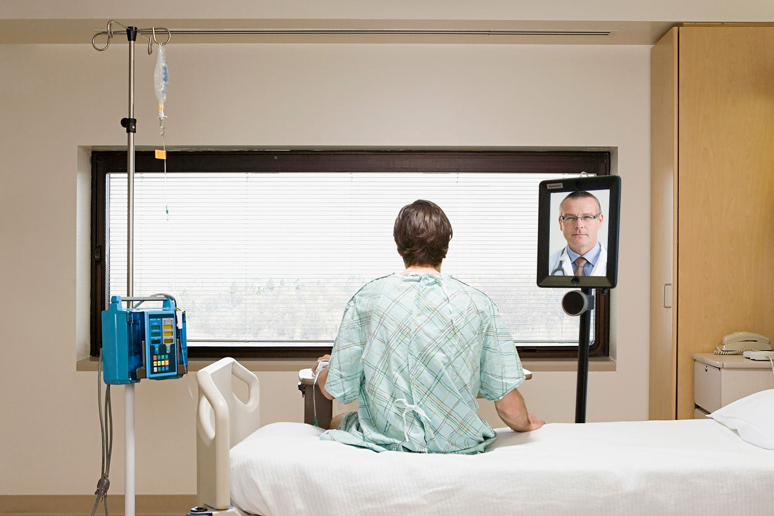 A patient sits on a hospital bed, talking to a doctor on a screen.