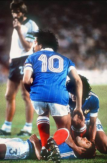 French defender Patrick Battiston lies on the ground as midfielder Michel Platini (10) and forward Didier Six.