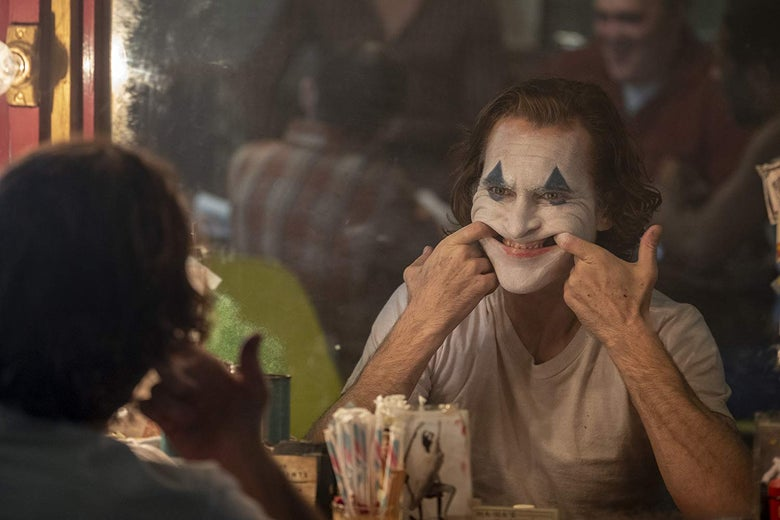 Looking into a mirror with his face painted like a clown, Joaquin Phoenix uses his fingers to manipulate his mouth into a smile.