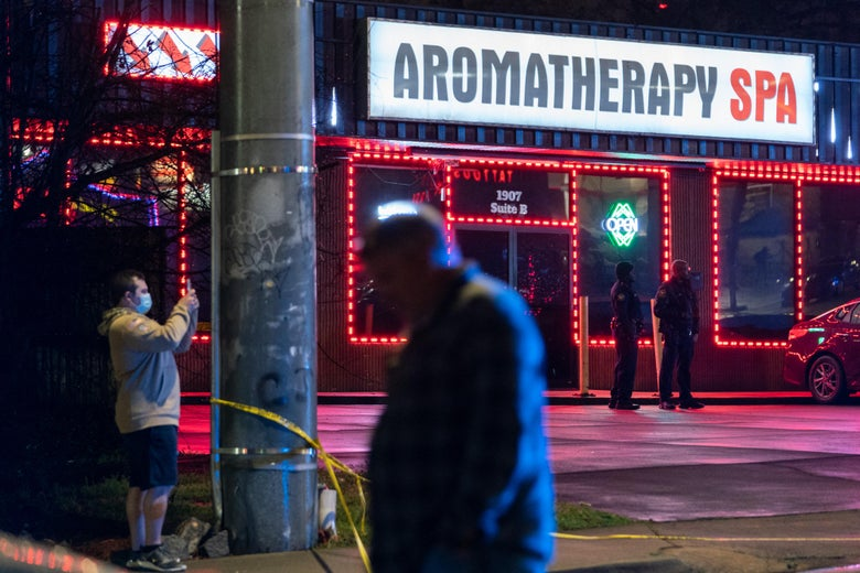 """A brightly lit sign says """"Aromatherapy Spa"""" on a building whose windows are outlined in red lights. Two law enforcement officers stand in front. It's dark outside, and a person walks in the foreground."""