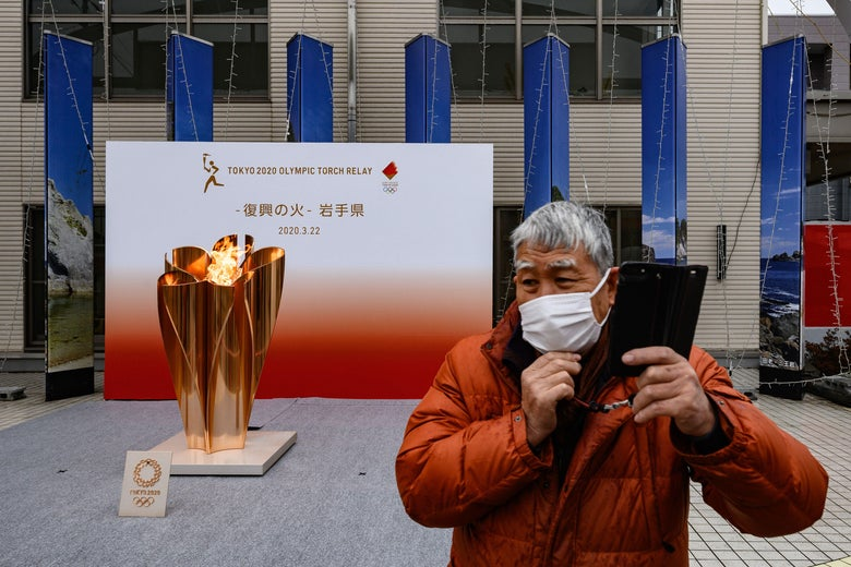 A man wearing a face mask stands in front of the Tokyo 2020 Olympic flame being displayed outside Miyako railway station, Iwate prefecture on March 22, 2020, after arriving from Greece.
