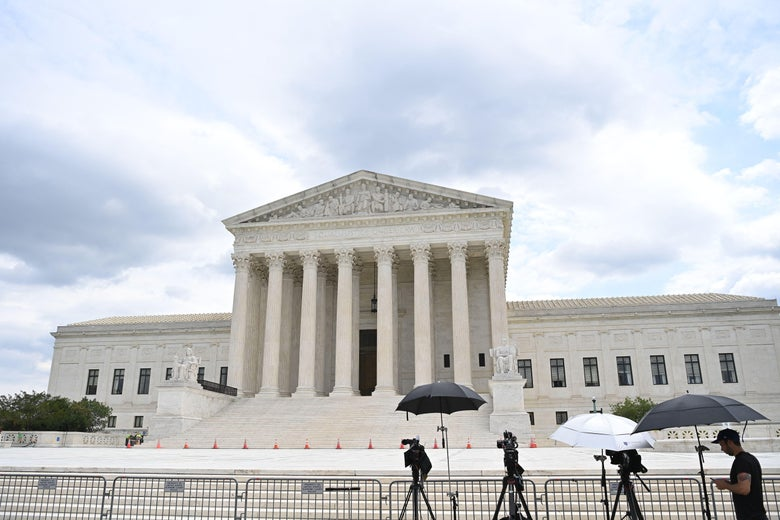 A person sets up umbrellas and cameras on the fence in front of the Supreme Court.