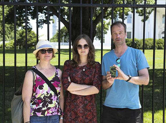 A Swedish family pose in front of the White House while Dad photographs me on his iPhone.