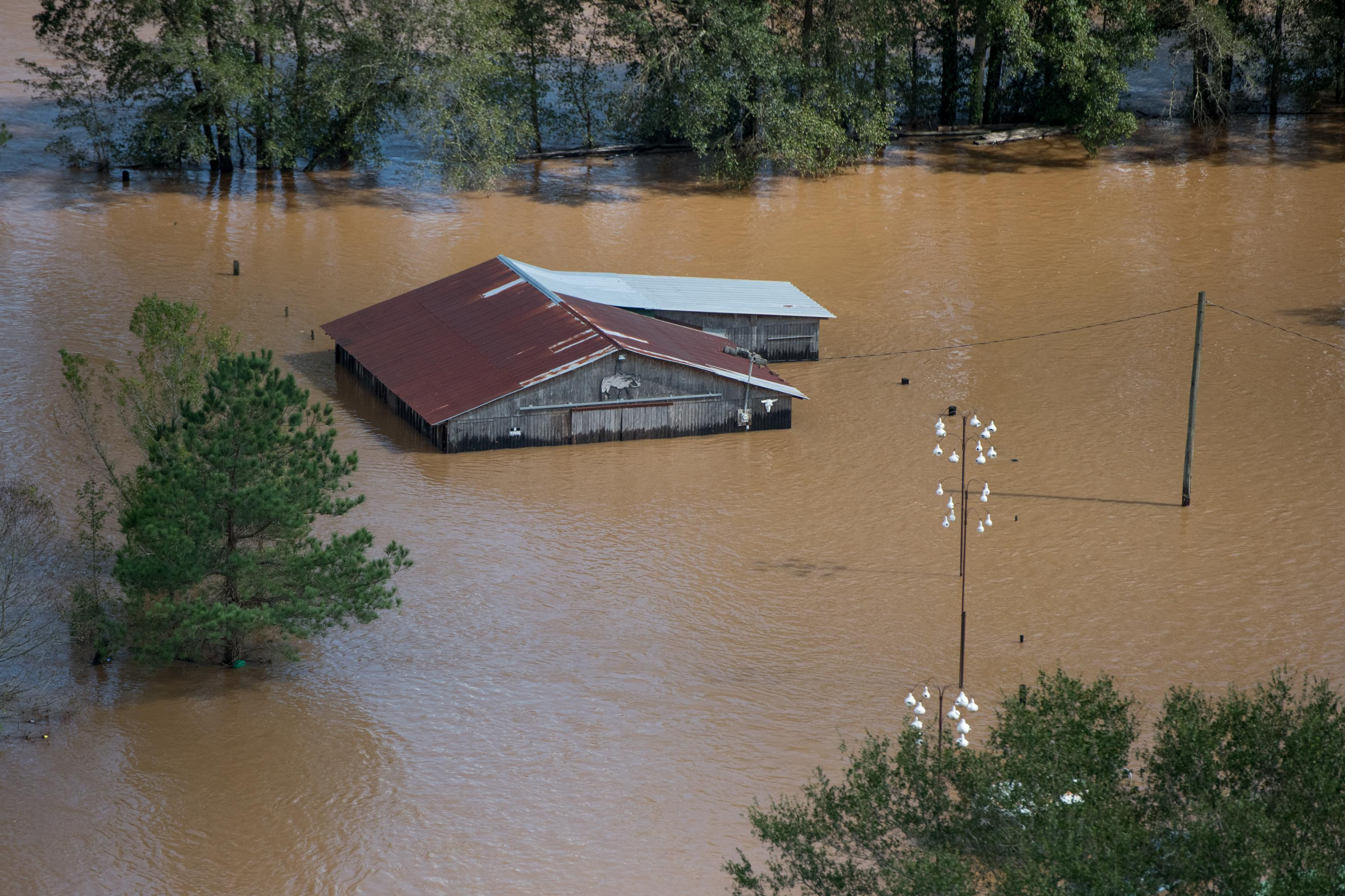An aerial shot of a roof of a barn surrounded by brown flood waters