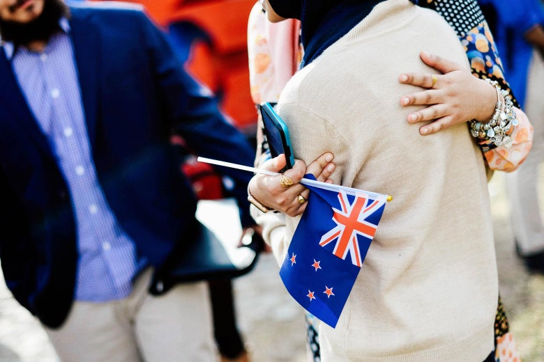 A woman in a headscarf is hugged by another woman holding a small New Zealand flag.