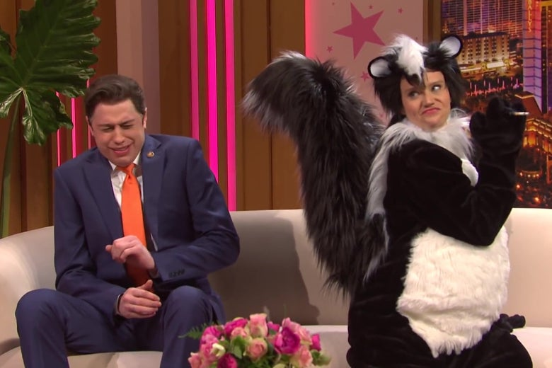 A still from Saturday Night Live, showing Pete Davidson dressed as congressman Matt Gaetz, sitting on a talk show set couch next to Kate McKinnon as cartoon skunk Pepé Le Pew. McKinnon is spraying Davidson.