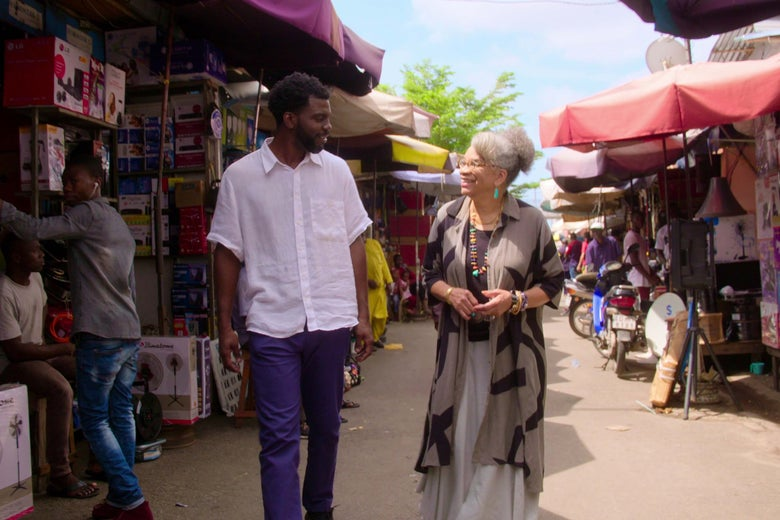 Two people walk through a busy market.