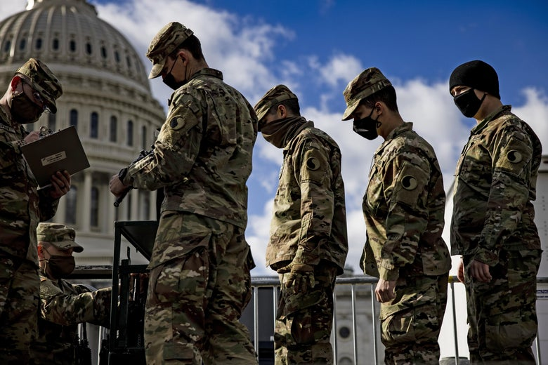 National Guardsmen near the Capitol receive their weapons.