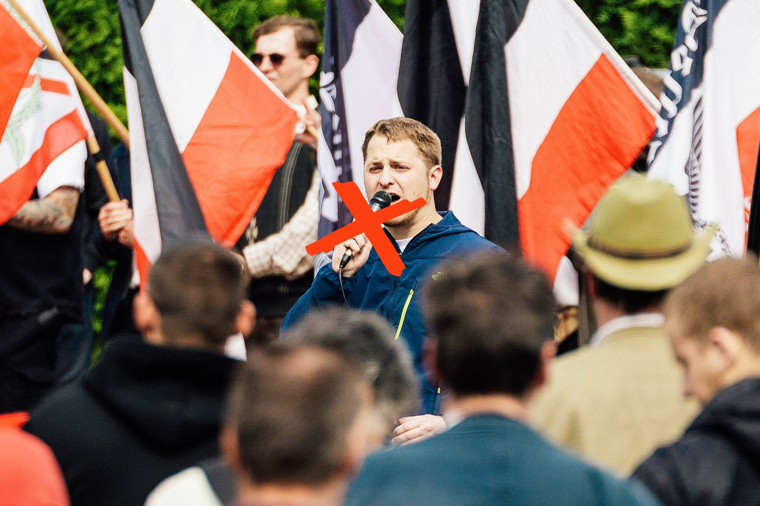 A neo-Nazi giving a speech at a rally, with an illustrated red X over his face.