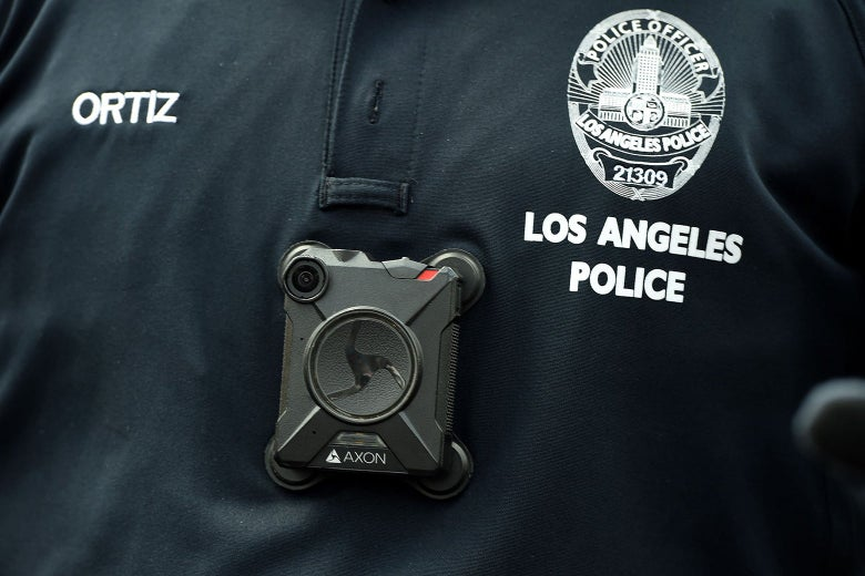 A close-up on a body camera attached to a police officer's shirt.