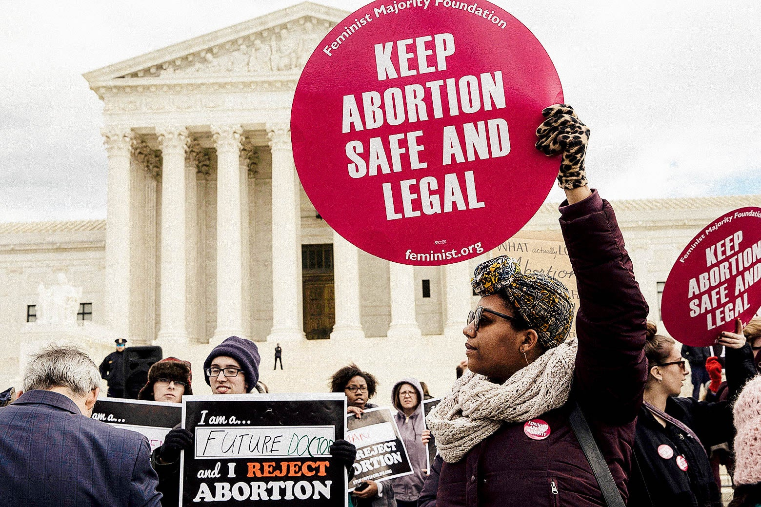 "In front of the Supreme Court, a crowd of abortion rights supporters holding signs reading ""KEEP ABORTION SAFE AND LEGAL"" and anti-abortion activists holding signs reading ""I am a future ___ and I REJECT ABORTION."""