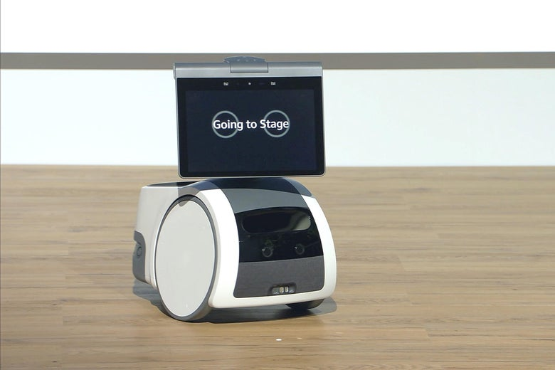 """A small wheeled robot with a display screen that says, """"Going to stage"""" and a cup holder in the back."""