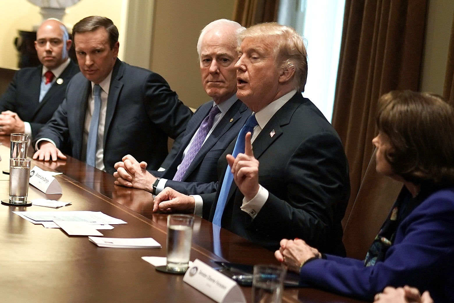 U.S. President Donald Trump (4th L) speaks as (L-R) Rep. Brian Mast (R-FL), Sen. Christopher Murphy (D-CT), Senate Majority Whip Sen. John Cornyn (R-TX) and Sen. Dianne Feinstein (D-CA) listen during a meeting with bipartisan members of the Congress at the Cabinet Room of the White House February 28, 2018 in Washington, DC.