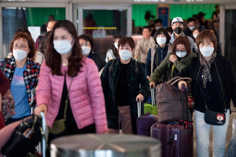 Airline passengers walk while carrying roller bags and wearing protective masks.