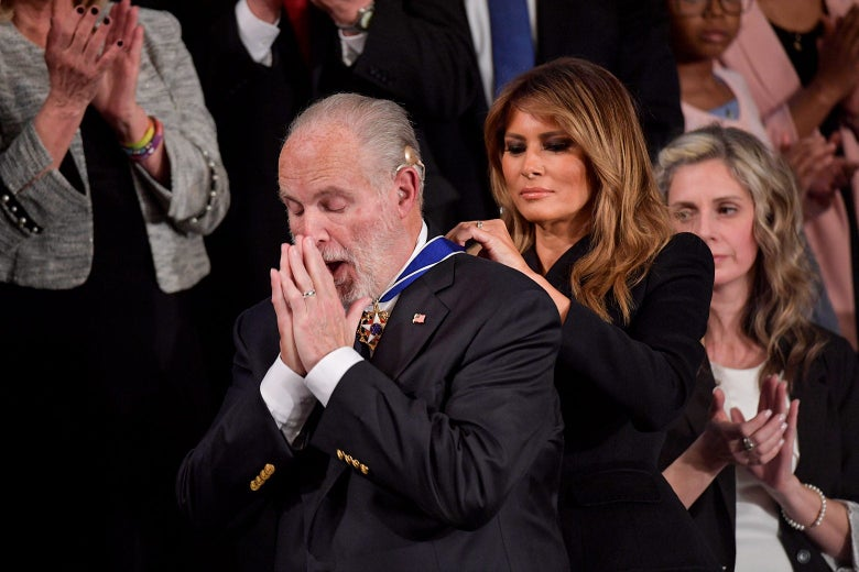 Melania Trump puts a medal around Rush Limbaugh's neck as he holds his hands to his face.