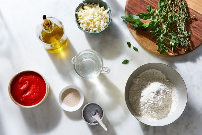 Small bowls of cheese, tomato sauce, olive oil, flour, and greens on a countertop.