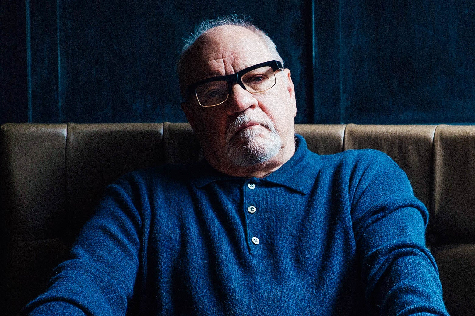 Paul Schrader in a blue shirt on a brown couch.