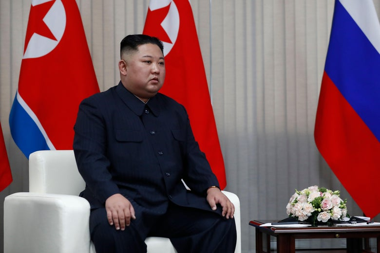Kim Jong Un sits in a chair in front of the North Korean and Russian flags