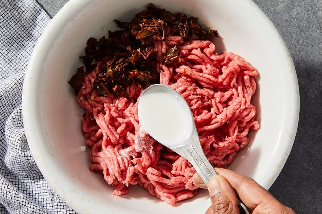 A spoon full of cream poised over a bowl of raw ground beef and chopped peppers.
