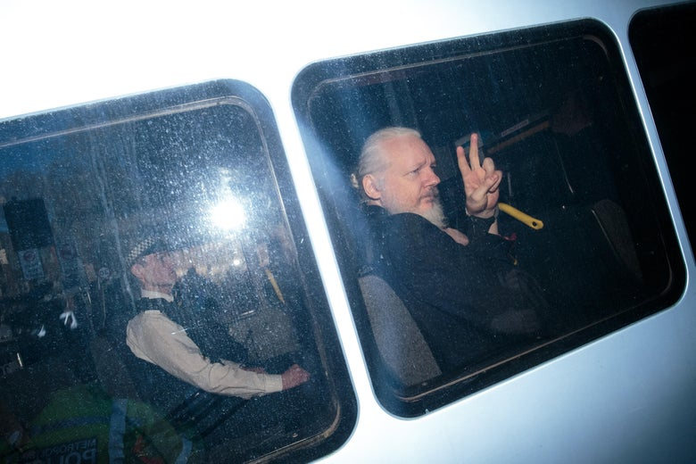 Julian Assange holds up a peace symbol as he is driven in a police vehicle in a grainy photo.