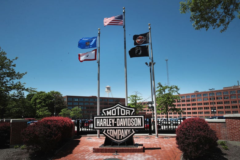 The American flag and several others fly over a Harley-Davidson sign in front of two red buildings on a corporate campus.