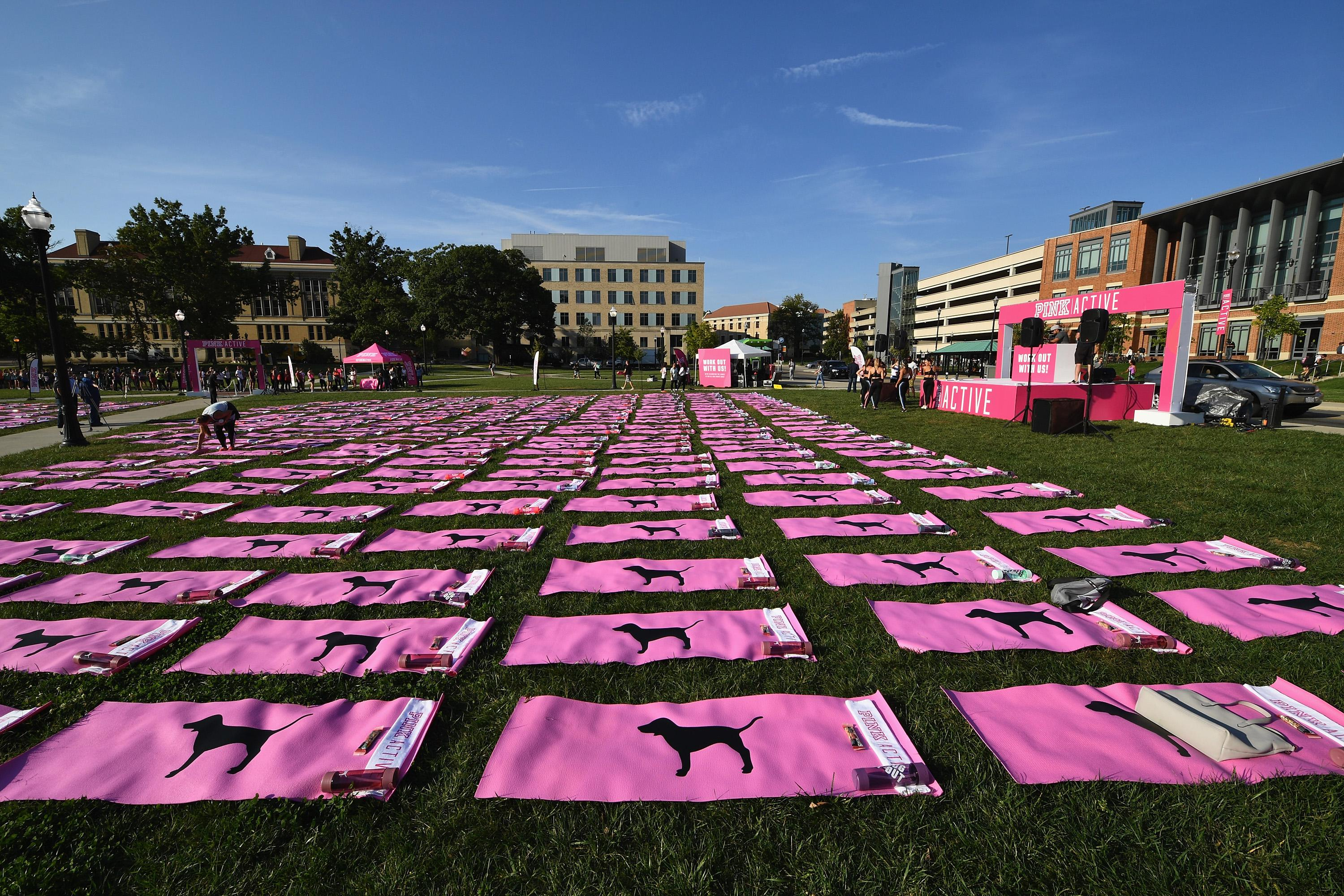 A view of the campus at Ohio State University, where Victoria's Secret's Pink held an event. A grassy field is covered in pink yoga mats, and there is a pink stage at the front of the field.