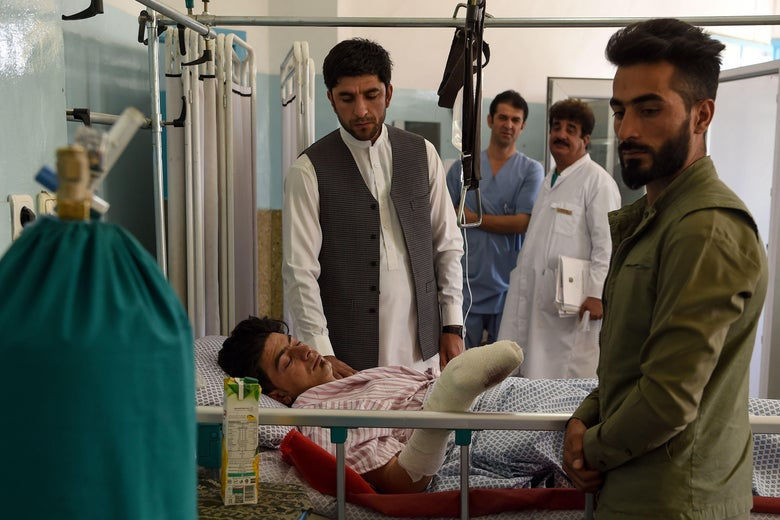 A wounded man receives treatment as people gather around him at the Wazir Akbar Khan hospital after a deadly bomb blast in a wedding hall in Kabul on August 18, 2019.