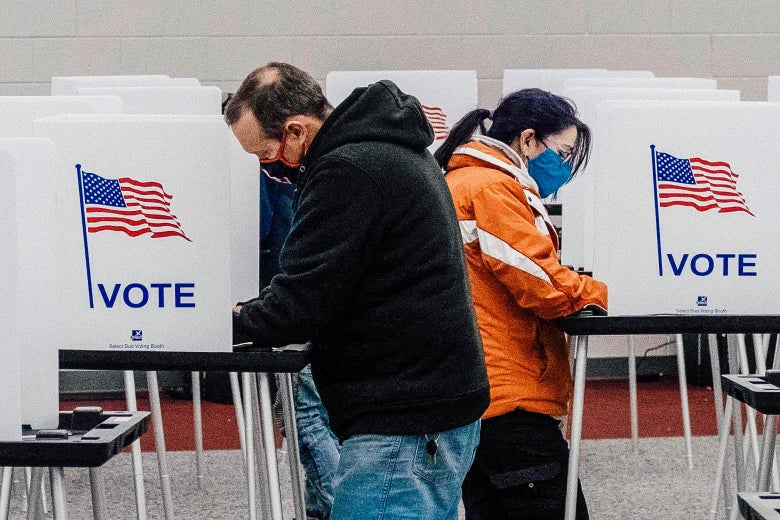 Two people stand at voting booths at Mott Community College