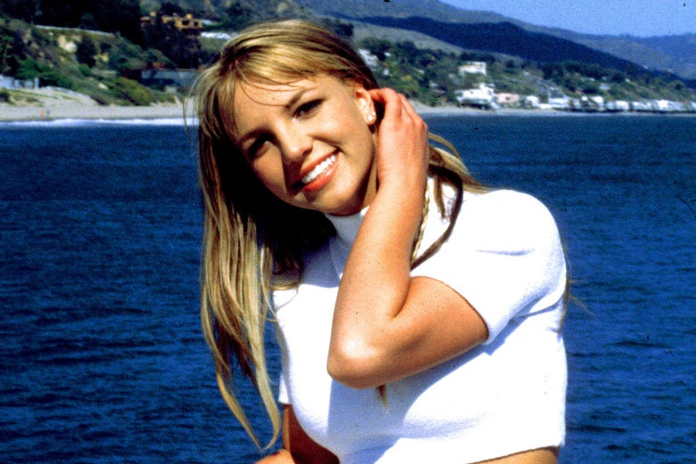 Britney Spears smiles and tucks a strand of hair behind her ear while she stands in front of the ocean wearing a white crop top.