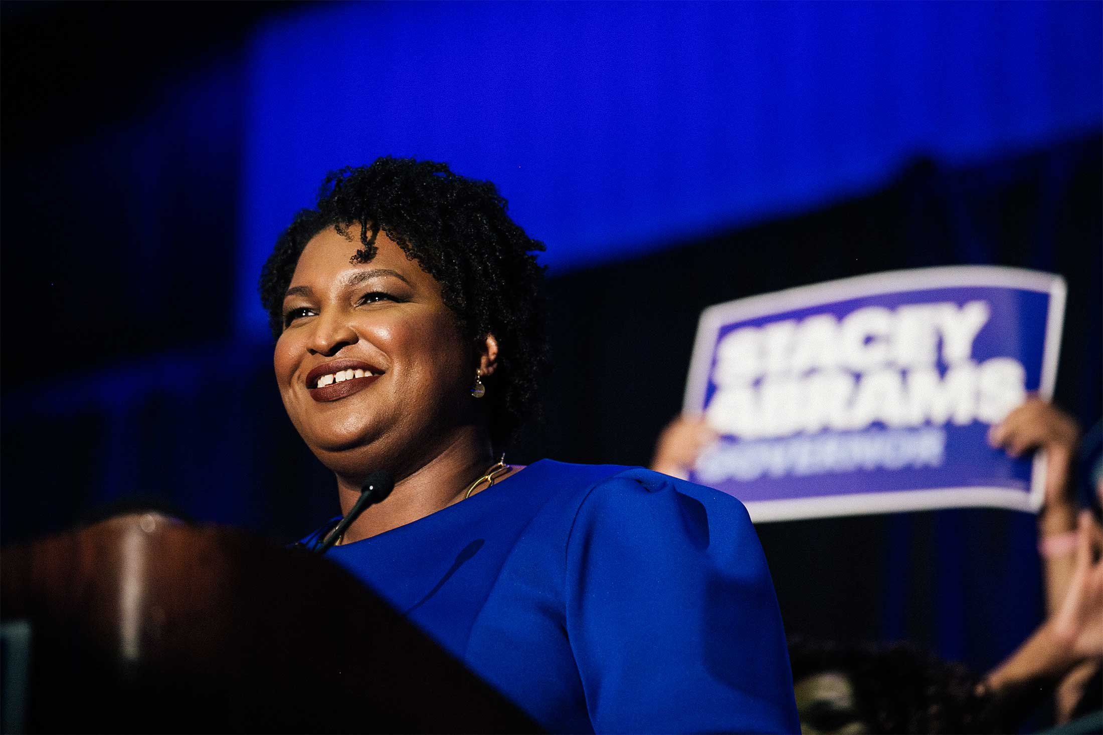 Stacey Abrams smiles from behind a podium.