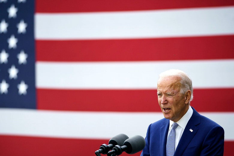 Joe Biden speaks into two microphones while standing in front of a U.S. flag.
