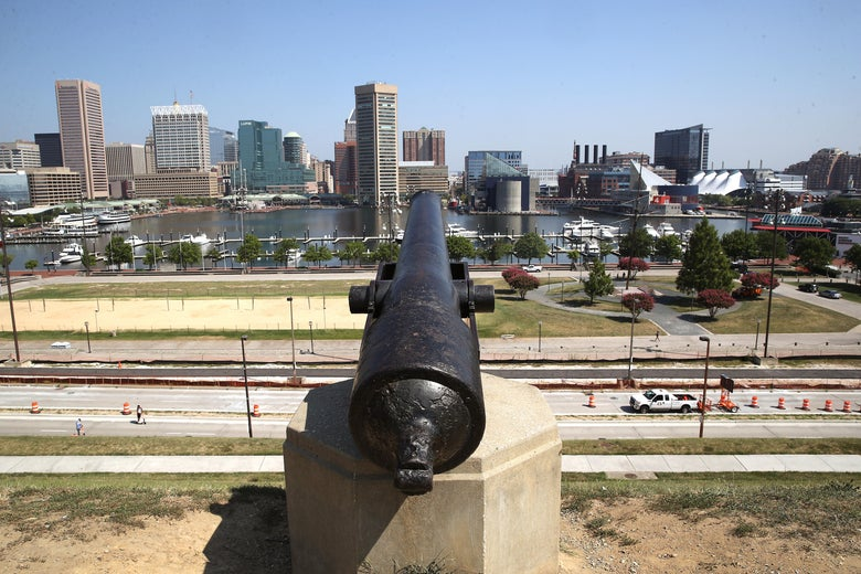 A cannon pointed at the Baltimore skyline on a sunny, cloudless day
