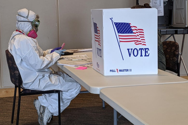 A person in a full-body hazmat suit sits at a table beside a voting booth
