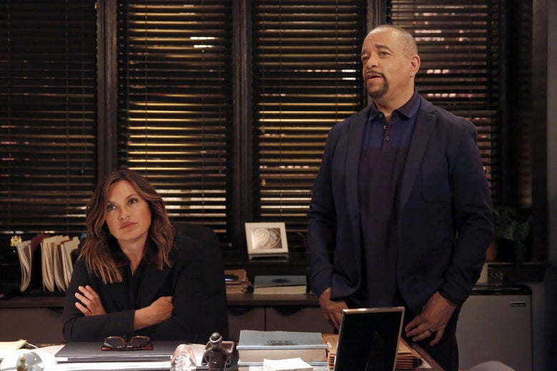 Mariska Hargitay and Ice-T stand in an office in front of a window with the blinds drawn.
