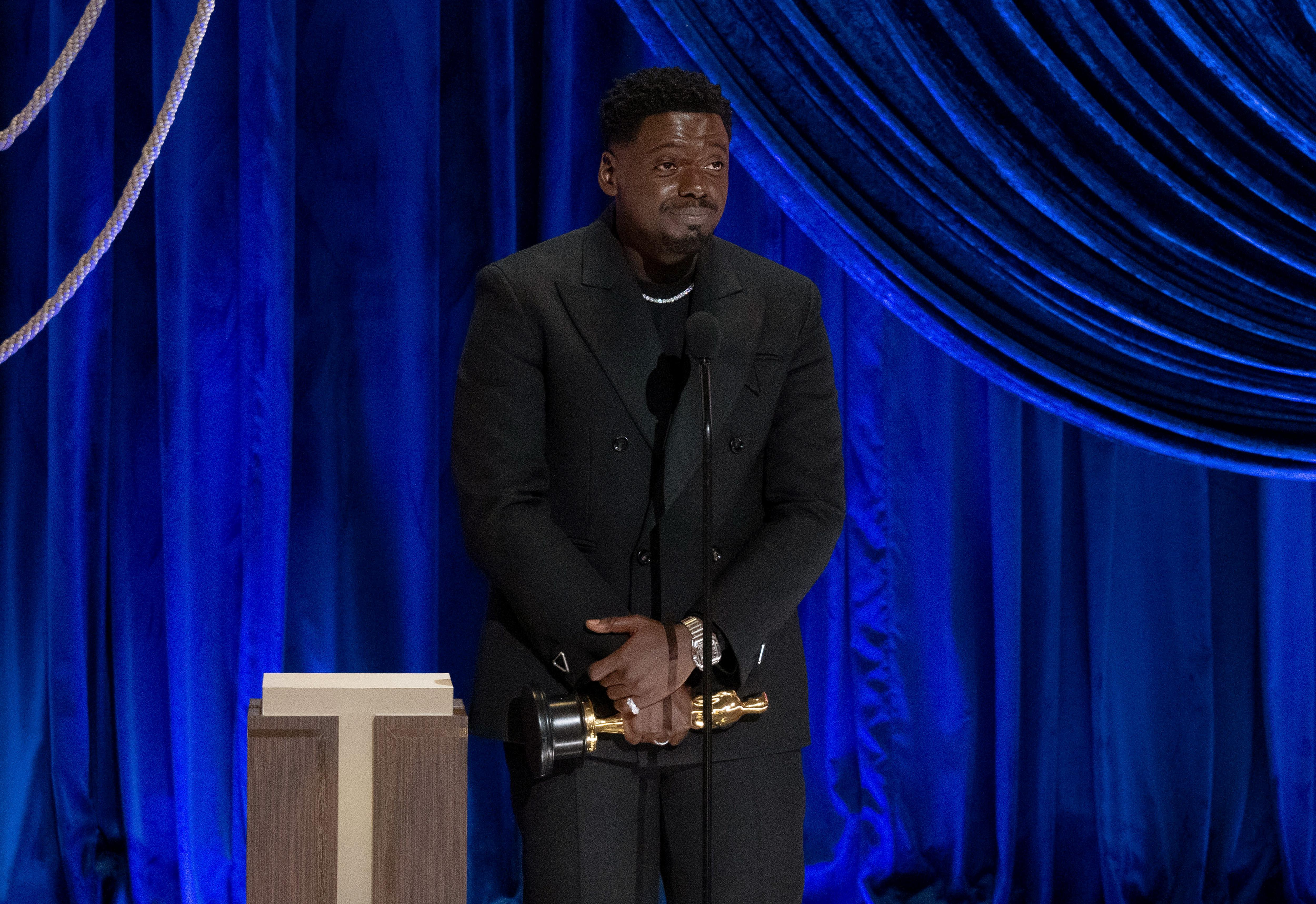 Daniel Kaluuya, looking stylish, holding his Oscar