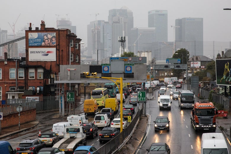 London's Canary Wharf skyline is seen as vehicles line up during the city's morning rush hour.