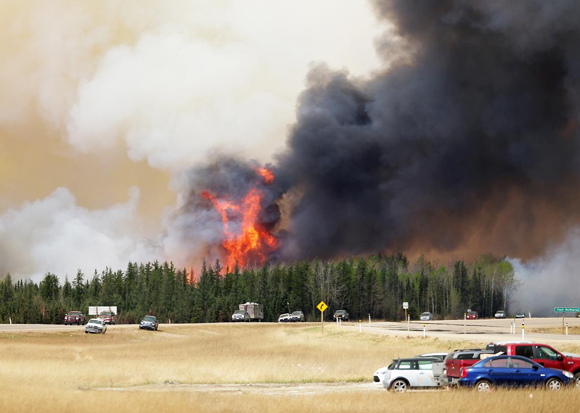 A convoy of evacuees drives  south as flames and smoke rises along the highway near  near Fort McMurray, Alberta on May 6, 2016.