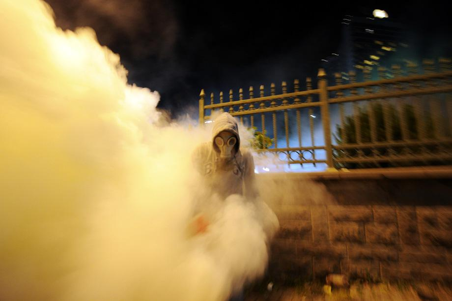 A protestor runs away from tear gas during clashes with Turkish riot policemen between Taksim and Besiktas in Istanbul on June 3, 2013 during a demonstration against the demolition of the park.